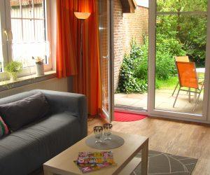 Wohnzimmer mit Zugang zur Terrasse der Ferienwohnung Muschel in Carolinensiel