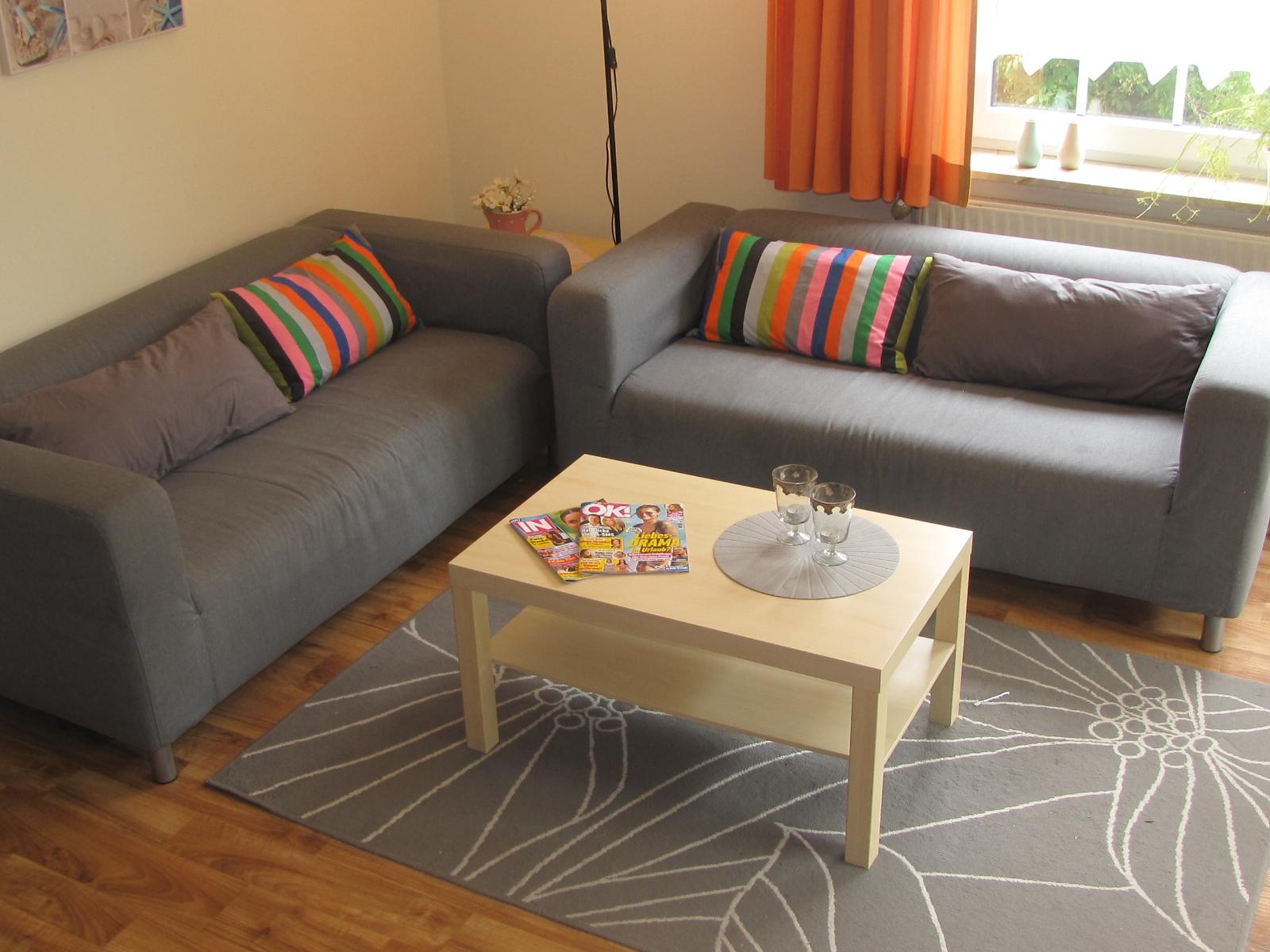 Wohnzimmer mit Couchgarnitur in der Ferienwohnung Muschel in Carolinensiel